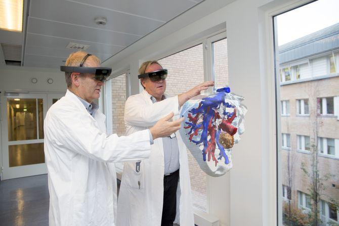 Leder for teknologisk forskning ved Intervensjonssenteret på Oslo universitetssykehus, Ole Jakob Elle og kirurg Bjørn Edwin demonstrerer HoloLens-teknologien.