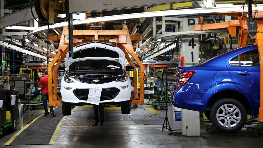 En Chevy Bolt (hvit) på produksjonslinja sammen med en bensindrevet Chevy Sonic sedan.