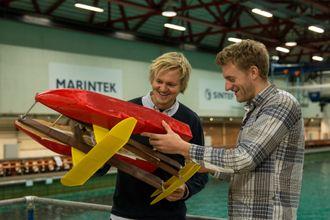 John Martin Kleven Godø (t.v) og Fredrik Storflor Moen med et modellskrog med Flapping Foil ved havbassenget på Marintek.