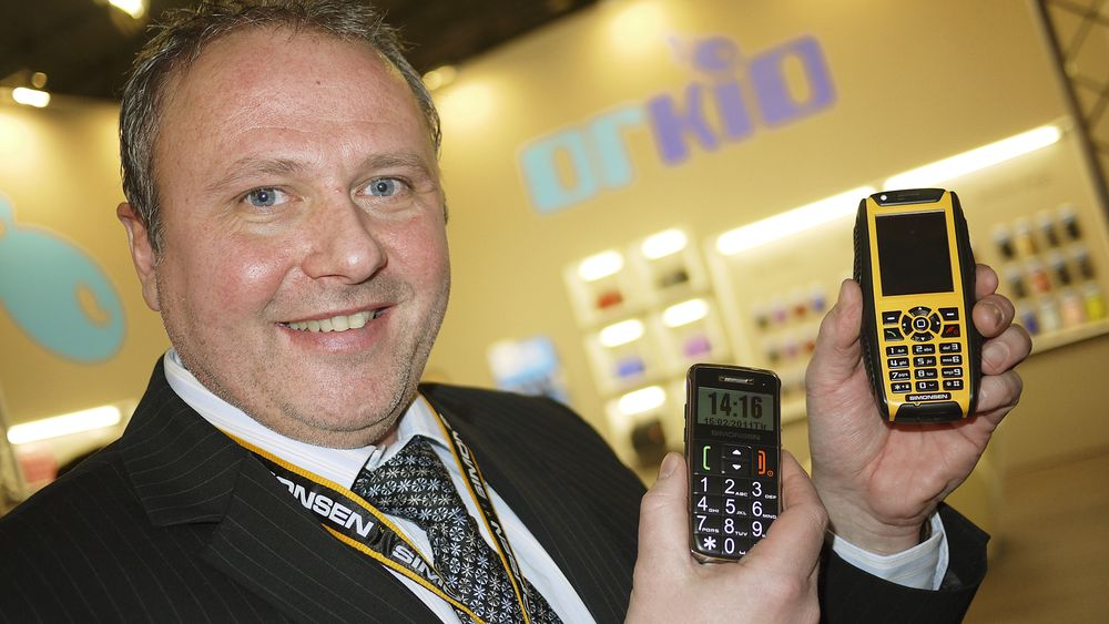 Administrerende direktør Roger Bakke i TeleD AS med seniortelefonen BB200 og Freeway F-510 for robust bruk. I bakgrunnen utstillingen til veskeleverandøren Orkio. Foto: Stian Sønsteng