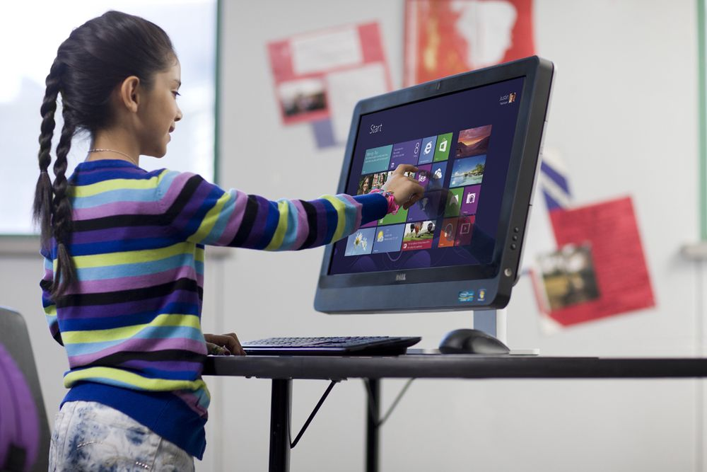 Young girl using Dell AIO desktop computer in elementary school classroom.