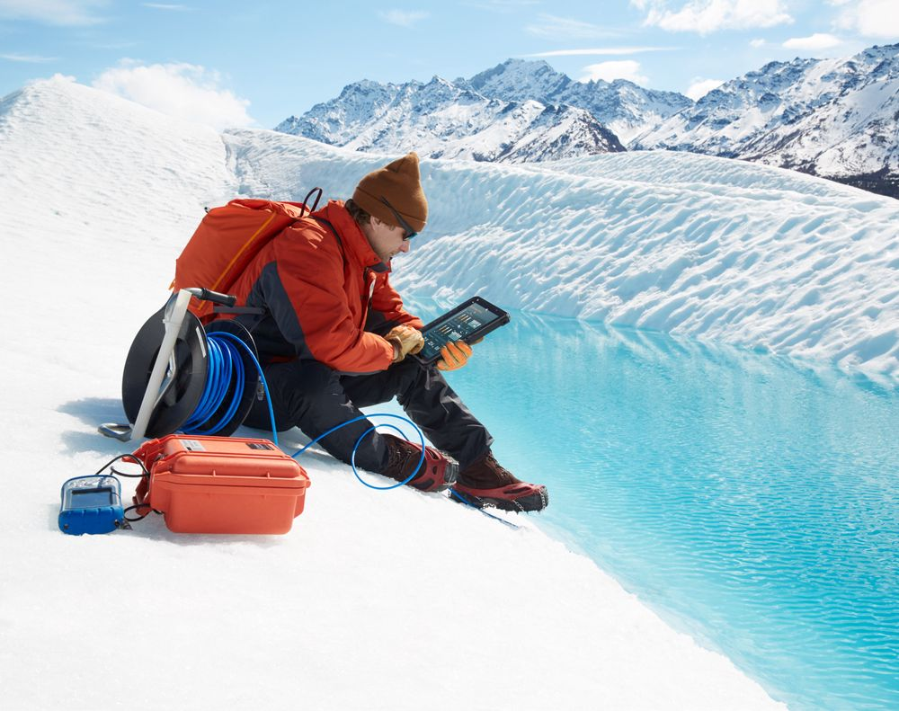 Man wearing sunglasses, protective jacket, gloves and cramp-on ice climbing shoes seated on a glacier holding a Dell Latitude 12 Rugged Tablet (Model 7202) computer. TTT environmental instruments case and measuring tape can be seen on the ice next to him with a snowy mountain in the background.