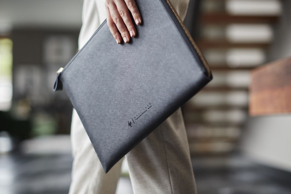 "Woman holding the HP Spectre 13.3"" Split Leather Sleeve"