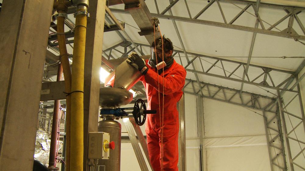 Her tilfører forsker Øyvind Langørgen metalloksid til reaktoren.