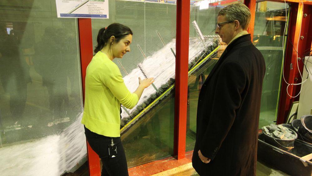 NTNU-stipendiat Priska Helene Hiller forklarer energiminister Terje Søviknes om forskning på plastring av fyllingsdammer (i bakgrunnen) i NTNUs vassdragslaboratorium.