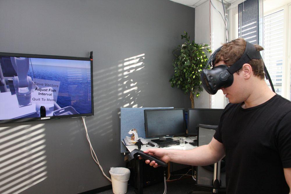 Forsker Jonathan Dyrstad bruker VR-teknologi når han skal lære roboten å gripe fisk.