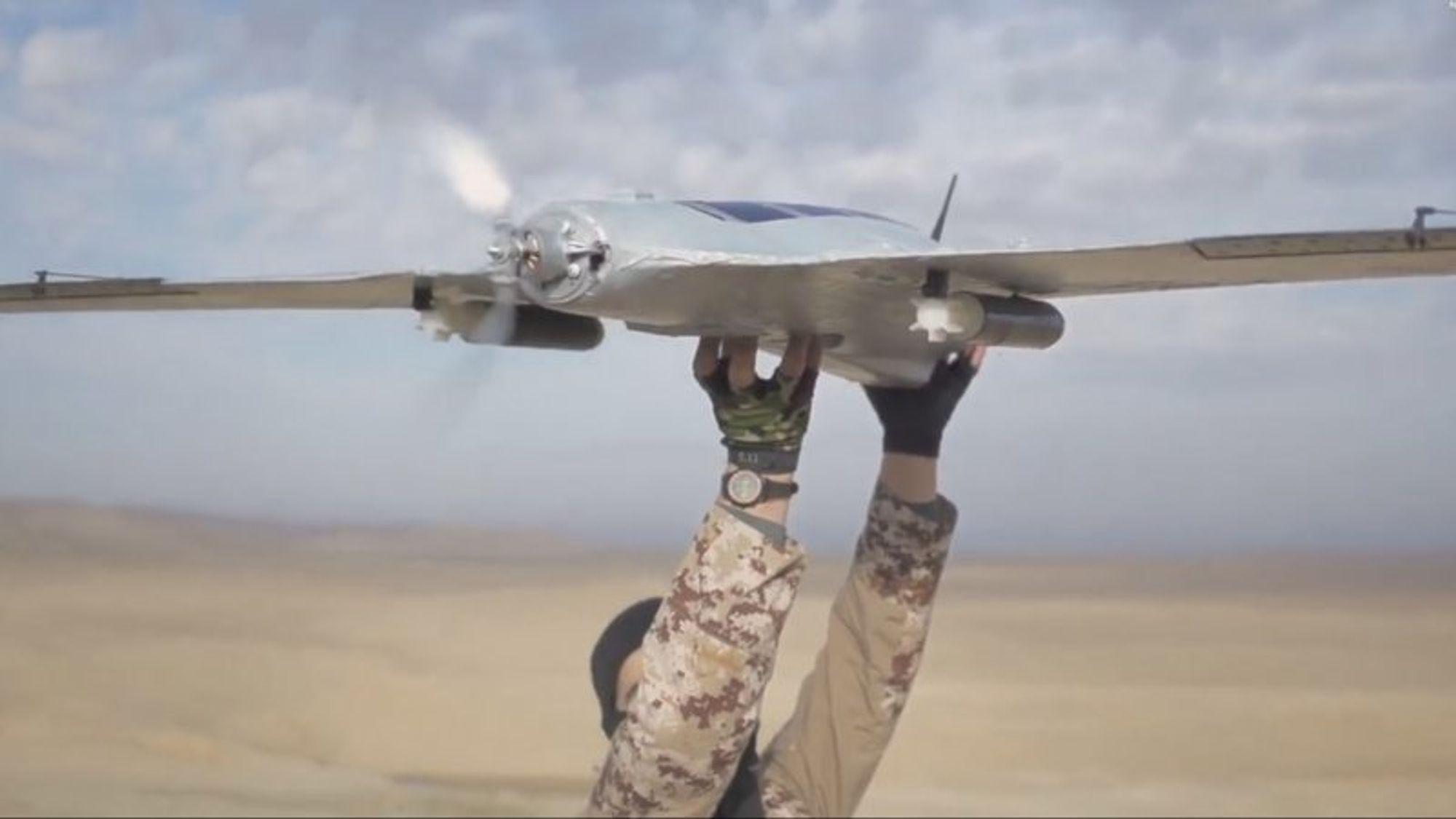 Et stillbilde fra en IS-video, hvor en kriger er i ferd med å sende en drone av gårde med granater under vingene.