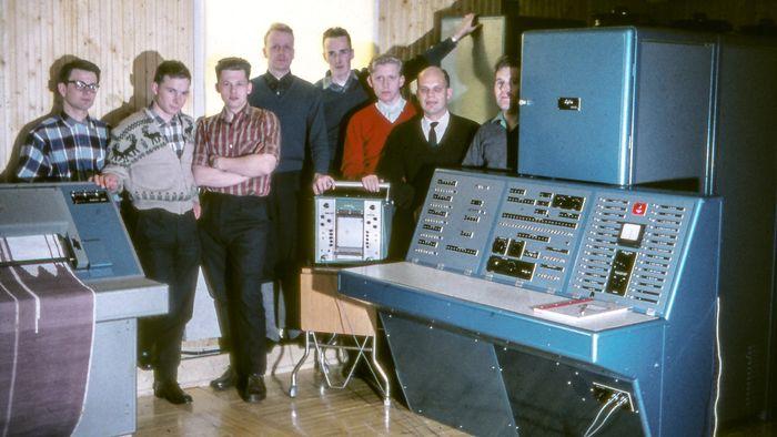 Siffergruppen anno 1962 ved sin første maskin Lydia. Den besto av fire skap fulle av elektronikk‐kort. Fra venstre: Per Bugge‐ Asperheim, Svein Strøm, Per Klevan, Lars Monrad Krohn, Per Bjørge, Asbjørn Horn, Olav Landsverk, Yngvar Lundh.