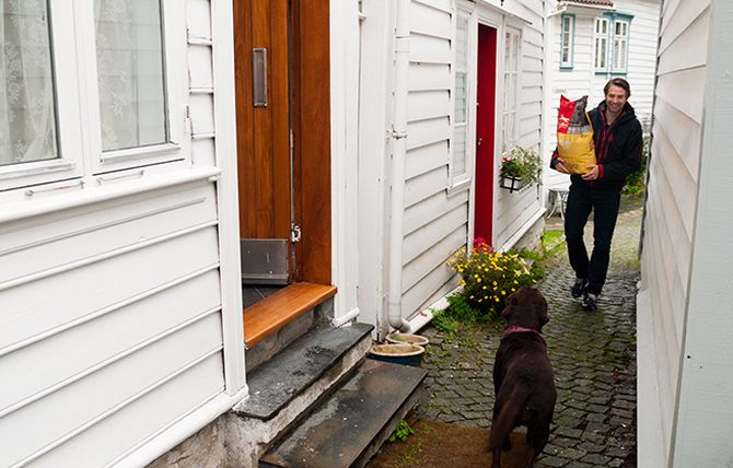 Trond Saure leverer fôr helt hjem på døren til labradoren Leia.