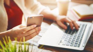 Kvinne som ser på mobiltelefonen samtidig som at hun skriver på en PC.
