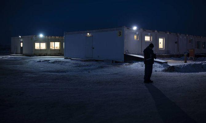 En asylsøker prøver å ringe i mørket på det nye mottakssenteret på Høybuktmoen.