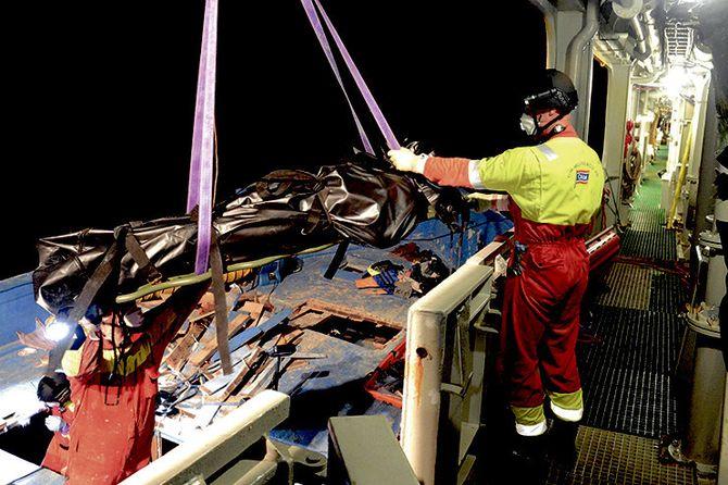 Tar de døde om bord: Mannskapet jobbet fra sen kveld til tidlig morgen med å hente ut lik fra en synkeklar trebåt.