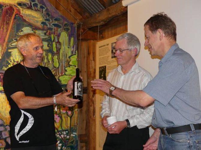 GÅVER: David Durkan frå Bergans, som også har operert lenge som fjellførar, overrekte Michael Smith og Erling Eggum to gåver kvar. Her får Eggum ei flaske Slingsbyvin. Rett nok tom, men vinen fanst i få eksemplar så flaska i seg sjølv er eksklusiv.