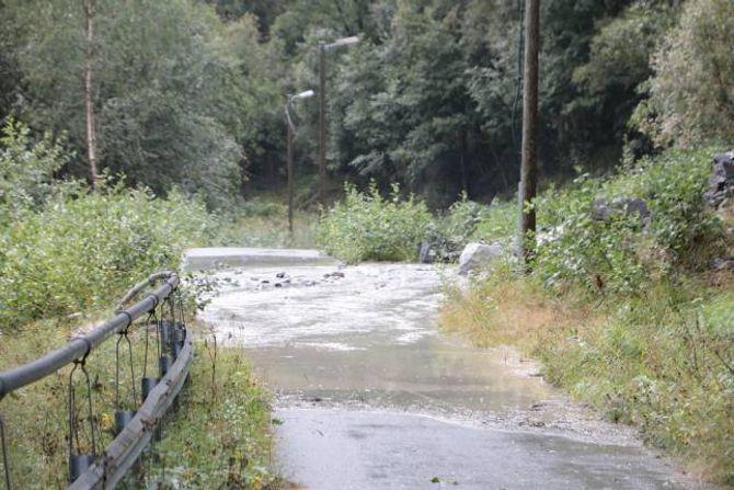 RENN OVER: Dammen som er laga til etter tidlegare ras er fylt opp av stein, noko som gjer at vatnet renn over stien.