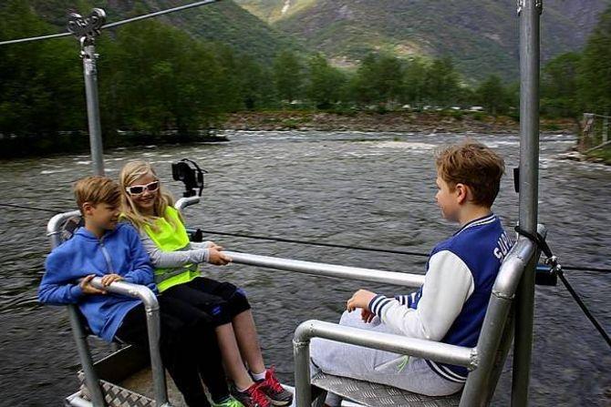 TAUBANE: David, Andrine og Casper på veg over elva i taubane.