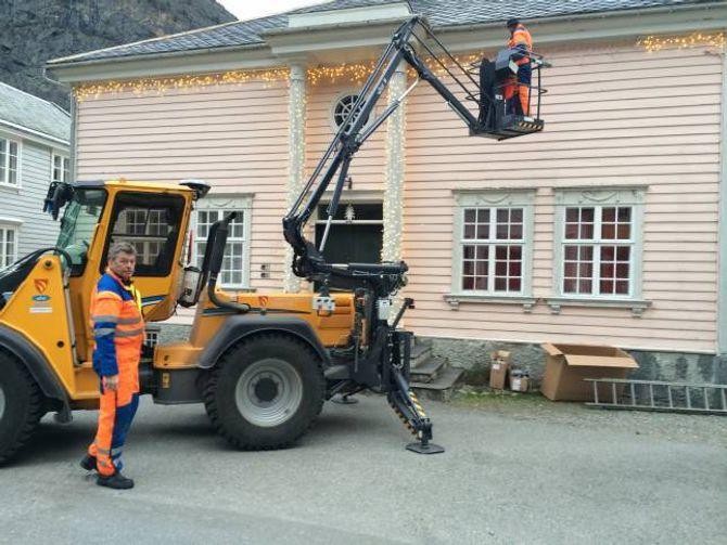 GAMLE BAKERIET: Gunnleif Haugen (frå venstre) og Bjørn Fodnes heng opp lys langs med mønet og stolpane på bygget.
