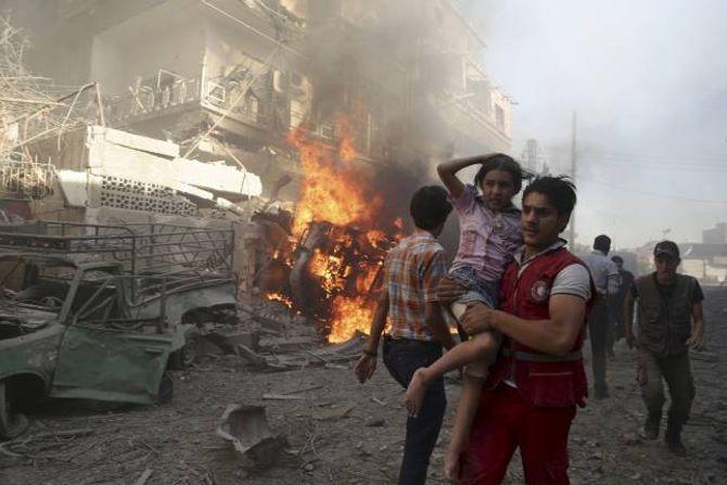 SYRIA: Hjelp til dei borgarkrigsramma i Syria står på agendaen hos mange av dei store hjelpeorganisasjonane denne jula. På biletet ber ein Raude Halvmåne-tilsett ei jente vekk frå eit bombeangrep.