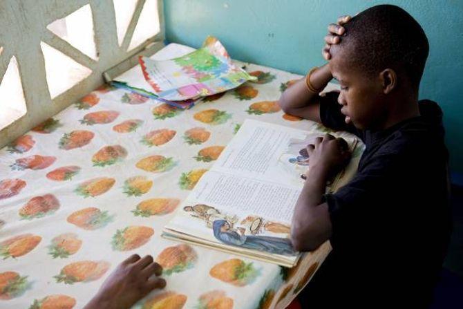 FASTE BIDRAG: Mange nordmenn gir faste månadlege bidrag til ein av faddarorganisasjonane. Her les ein gut lekser i ein SOS-barneby i Gambia.