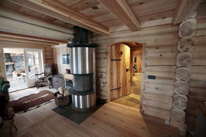 SOLIDE VEGGER: Tømmerstokkane er godt synlege overalt i heimen til Knut Kolstad.