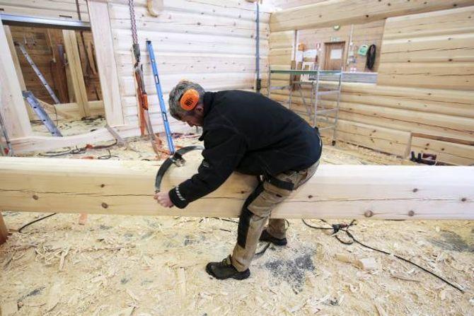 LAGAR SPOR: Ingar Bekkeseth, som er medeigar i Nore Laft, bruker meddragskniv til å lage medfar (spor) på undersida av tømmerstokken.