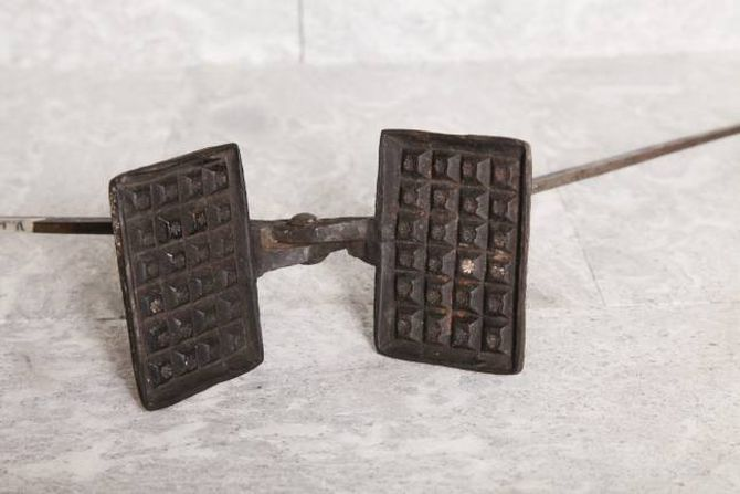 Eit gammalt vaffeljern. Slike fanst her i landet allereie på 1600-talet. Dei var visstnok relativt enkle å lage og det gjekk med lite jern, slik at fleire kunne ha råd til å skaffe seg denne «moderne» kjøkenreiskapen. Foto frå boka: Bjarne Fossøy.