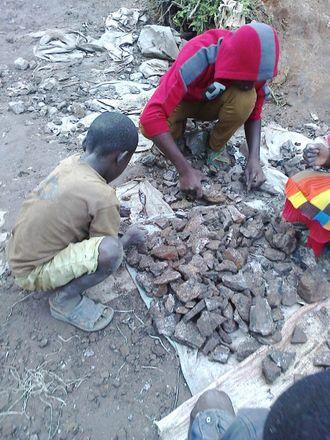 Barn sorterer og knuser koboltmalm i Kasulo Kolwezi i DRC.