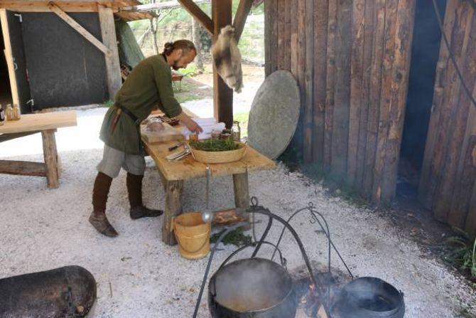 KAFÈ: Viking-John gjer i stand til opninga av vikingkafèen; i grytene putrar grønsakssuppe og urtete