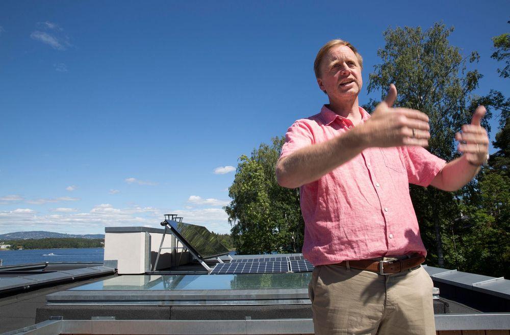 Bjørn Haugland på taket av huset sitt på Nesøya med solcellene i bakgrunnen.