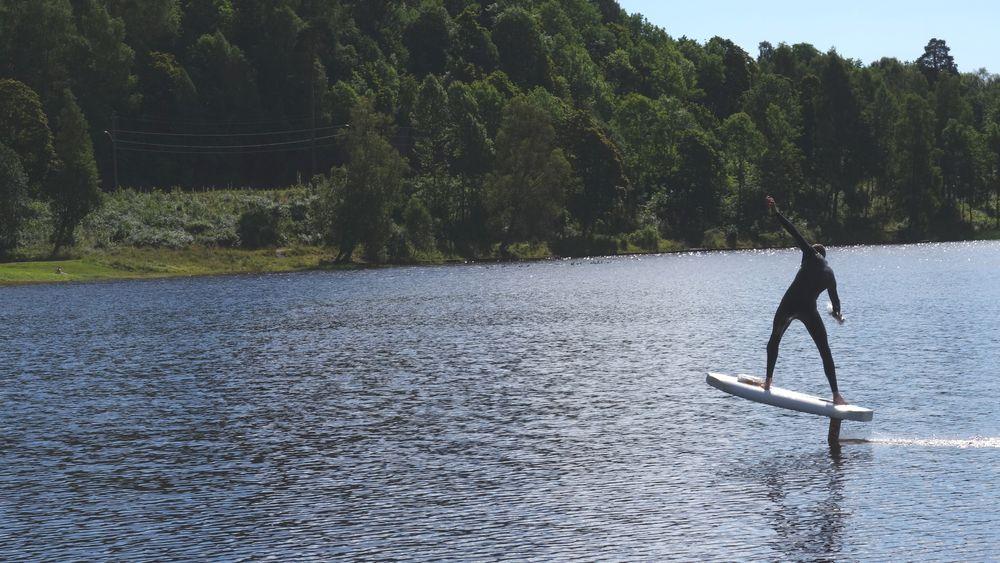 Brødrene Hiorth kan nå sveve over vannet på egenlaget hydrofoilbrett. Her får en kompis av brødrene prøve brettet.