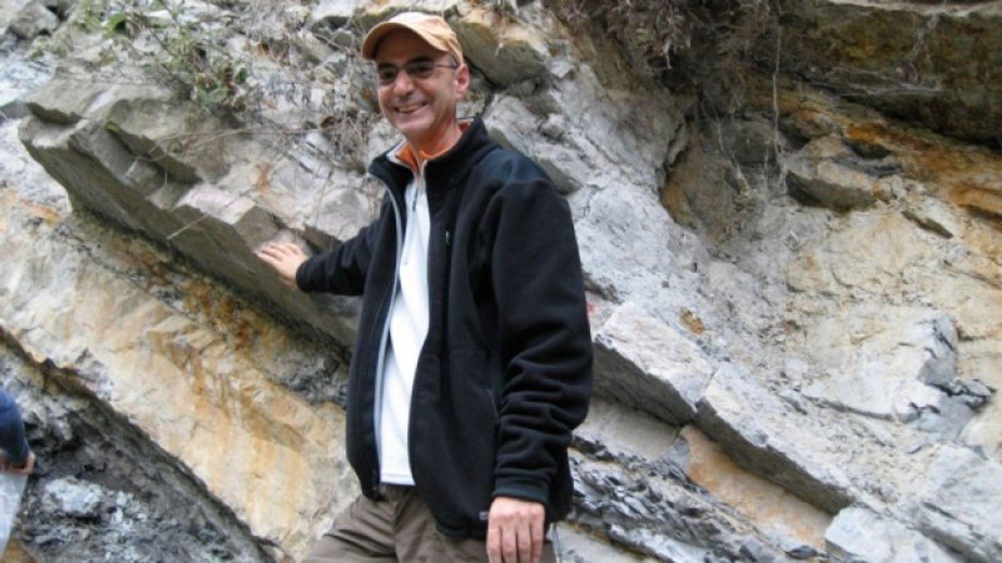 Daniel Rothman med høyre hånd plassert på et lag ved Xiakou i Kina. Laget markerer overgangen mellom de geologiske periodene perm og trias for cirka 252 millioner år siden, da nærmere 96 prosent av alle levende arter i havet døde ut.