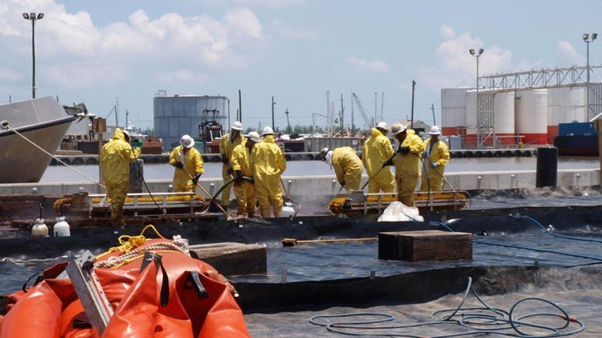 Fotoet er fra mai 2010, da arbeidere i havna i Venice i staten Louisiana vasker olje og dispergeringsmidler av utstyr ved hjelp av høytrykksspyling.