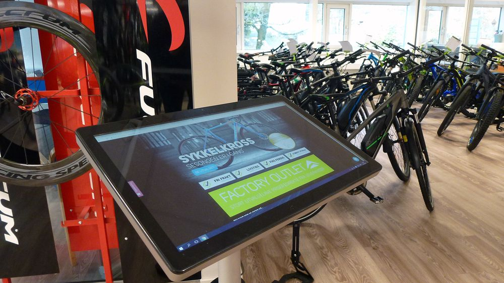 På dette bildet ser du to av de viktigste fremtidselementene til Meridastore.no. Berøringsskjermer i butikker og elsykler. - Elsykler blir bare viktigere og viktigere for sykkelbransjen, fastslår Stian Steen-Olsen.