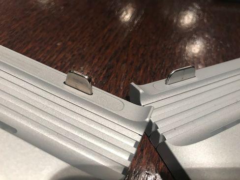 Den nye mekanismen for å feste skjermen til venstre, den gamle til høyre. Den nye er høyere og smalere, og skal gjøre det lettere å få skjermen løs fra tastaturdelen.