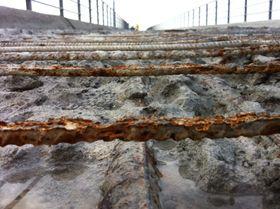 Bildet viser oversiden av dekket på Uttian bru. Brua hadde store skader i dekkeoverflaten etter kjøring med piggdekk og sterke klimapåkjenninger.