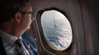 Olje og energiminister Terje Søviknes ser ut av flyvinduet på en av de fem flytende vindturbinene som utgjør Hywind Skottland.