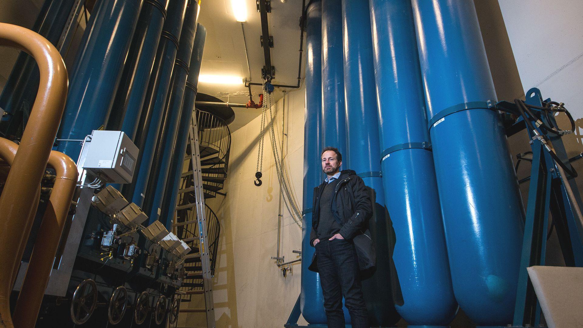 Bjarte Christoffersen står foran de enorme tankene med nitrogen, som driver enorme akkumulatorer til venstre.