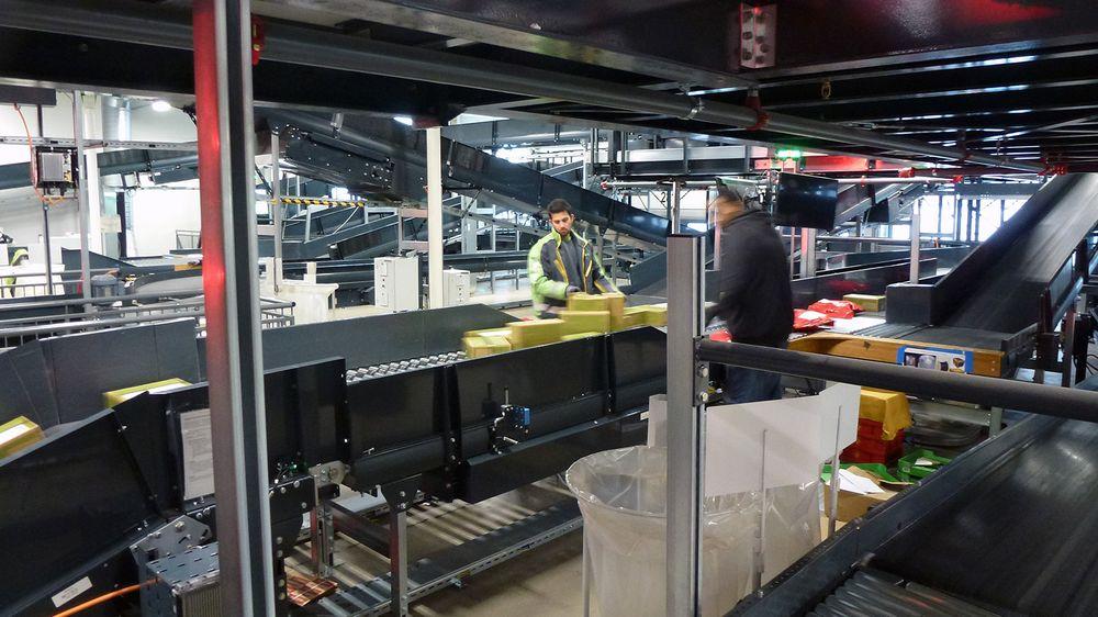 Ferske pakker singuleres og legges riktig med strekkoden opp. Tross automatisering er det fortsatt stort behov for menneskelige hender for å få posten frem.