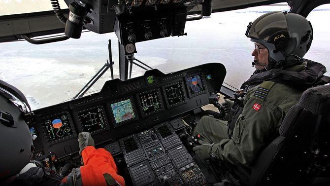 Inne i cockpit på et dansk EH101 i nærheten av basen i Roskilde. Venstrehånda er plassert på «collective»-håndtaket.