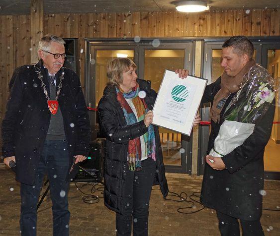 Det endelig beviset for at boligprosjektet er svanemerket overrekkes. Fra venstre ser vi ordfører i Spydeberg kommune Petter Schou, Anita Winsnes som er direktør i Svanemerket, og Jørn Regin Jaucis i Askim Entreprenør.