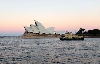 Sydney Operahus i solnedgang, sett fra sjøsiden. Fergen til Manly i forgrunnen.