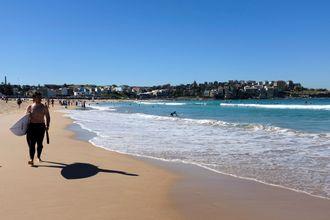 Surfer på Bondi Beach en solfylt høstdag.