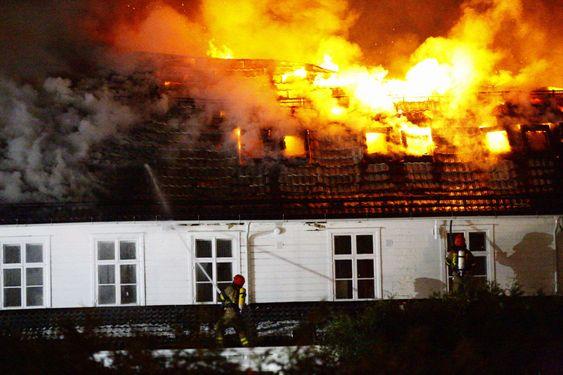 FLAMMEHAV: Brannmannskap kjempa søndag kveld for å hindra spreiing av brannen i det nær hundre år gamle trehuset Stedjetun på Stedje i Sogndal.