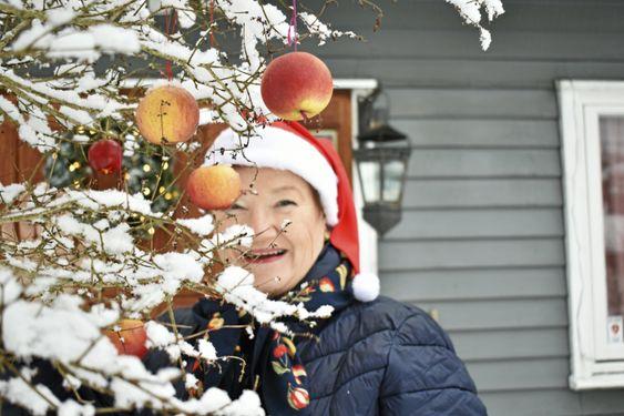 GLADE JUL: – Jeg elsker jul! Jeg er skikkelig julemenneske. Selv da vi bodde i Addis Abeba i Somalia, måtte jeg feire jul. Vi trakk for gardinene og tente lys i de gamle stearinlysholderne laget av tre, forteller Sylvi Graham (65), mens hun henger opp eplene på treet.