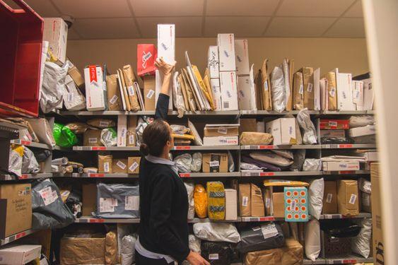 STORE MENGDER: Dette er bare en av de mange stappfulle hyllene med julepost som er på post i butikk hos Coop Mega på Kolbotn. Elena Simeonova er en av de som jobber på spreng for å sørge for at alle får pakkene sine.