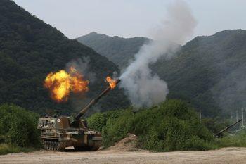 En kamuflasjefarget artillerivogn skyter slik at det står flammer og røyk ut av løpet.