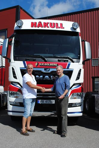 Steinar Solberg, eier og daglig leder i H. K. Solberg Transport AS (til høyre), mottar seks nye MAN TGX 26.580 fra Johannes Erlandsen, salgskonsulent for MAN Truck & Bus Norge AS i Kristiansand.
