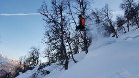 Mann hoppar på ski i laussnøen.
