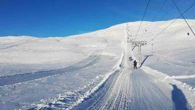 Bilete teken frå skiheis. Utsikt mot toppen som er dekka i snø.