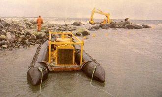 Drivaggregatet med pontonger. Bøyene markerer slangene til maskinen. Det grove materialet på stranden gir inntrykk av hvilke masser man graver i.