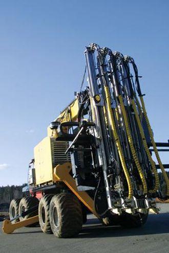 Bakpå sitter fire boretårn med matere og hammere fra Atlas Copco.
